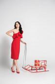 Mosolygós barna nő piros ruhában áll közel szánkó ajándék szürke háttér