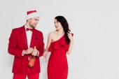 Usmívající se žena v červených šatech drží sklo v blízkosti přítele v Santa klobouk s lahví šampaňského izolované na šedé