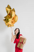Cheerful woman in red dress holding present and golden balloons on grey background