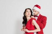 Muž v Santa klobouk a motýlek nosí náhrdelník na ženě v šatech se sklenkou šampaňského na šedém pozadí