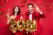 Mosolygó pár poharak pezsgő tartja léggömbök alakja 2021 számok alá eső konfetti vörös alapon