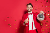 Stylish man in suit smiling at camera while holding disco ball and glass of champagne on red background