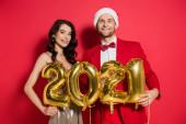 Usmívající se muž v Santa klobouk drží balónky ve tvaru 2021 čísla v blízkosti přítelkyně v šatech na červeném pozadí