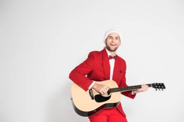 Young man in suit and santa hat smiling at camera while playing acoustic guitar on grey background