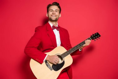 Cheerful man in suit playing acoustic guitar on red background