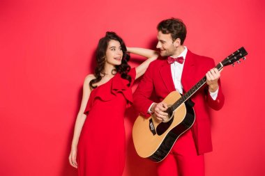 Smiling woman in dress looking at boyfriend playing acoustic guitar on red background