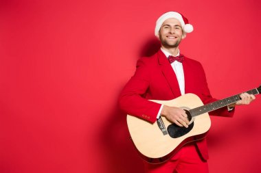 Smiling man in santa hat playing acoustic guitar on red background