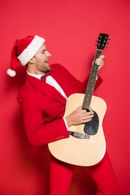 Positive man in santa hat playing acoustic guitar on red background
