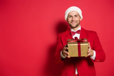 Positive man in santa hat and suit holding present with bow on red background stock vector