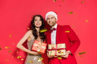 Cheerful couple with santa hat and presents looking at camera under falling confetti on red background stock vector