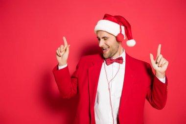 Noel Baba şapkalı heyecanlı adam kulaklıkla müzik dinliyor ve kırmızı arka planı işaret ediyor.