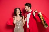 Stilvolles Paar mit einem Glas Champagner und Einkaufstaschen auf rotem Hintergrund