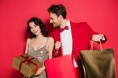 Stylový pár s úsměvem při držení dárek a nákupní tašky na červeném pozadí