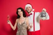 Mosolygós férfi télapó kalap gazdaság disco labda közelében barátnője poharak pezsgő piros háttér