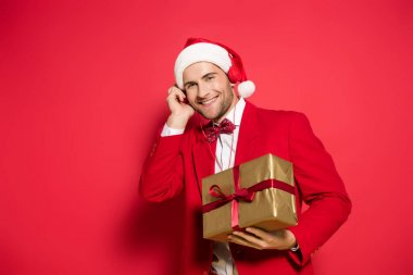 Smiling man in santa hat listening music in headphones and holding present on red background