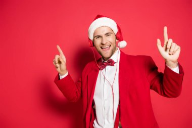Smiling man in santa hat and headphones pointing with fingers on red background