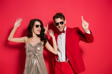 Stylish couple in sunglasses dancing on red background