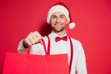 Shopping bags in hand of smiling man in santa hat on blurred background on red background stock vector