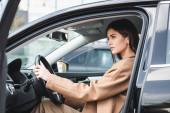 stylová žena v podzimním oblečení dívá pryč, zatímco sedí v autě na rozmazané popředí