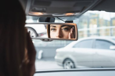 Woman in car touching face while looking in rearview mirror on blurred foreground stock vector