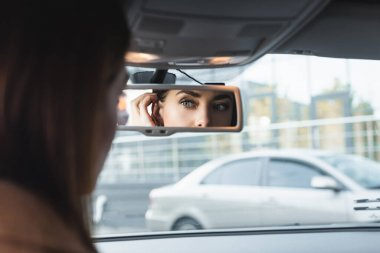 Woman fixing hair while looking in car rearview mirror on blurred foreground stock vector