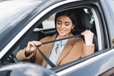 stylish woman in autumn outfit putting on safety belt while sitting in car on blurred foreground