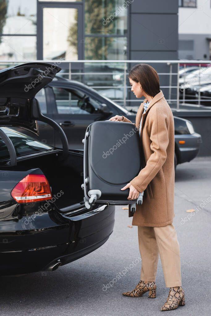 giovane donna in eleganti vestiti autunnali valigia di carico nel bagagliaio auto