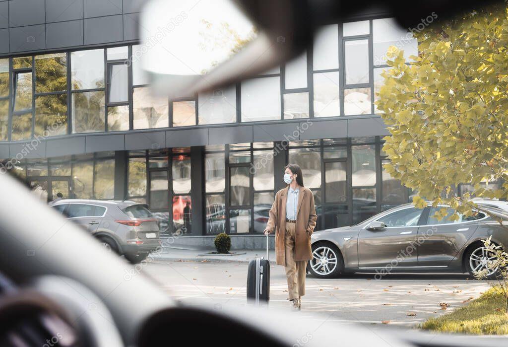 elegante donna in abito autunnale passeggiando lungo il parcheggio auto con valigia in primo piano sfocata
