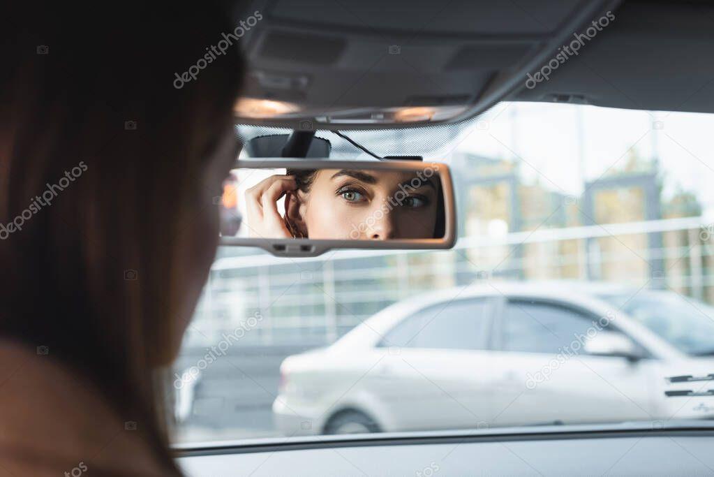 donna che fissa i capelli guardando nello specchio retrovisore dell'auto in primo piano sfocato