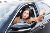 Unzufriedene Frau schaut aus Seitenscheibe und zeigt mit der Hand während Autofahrt auf verschwommenen Vordergrund