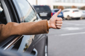 oříznutý pohled na ženu ukazující palec nahoru z postranního okna při řízení auta na rozmazaném popředí