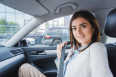 elegant woman smiling at camera while sitting in car and fixing seatbelt
