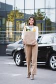 stylová mladá žena držící nákupní tašku s jídlem při chůzi podél parkoviště