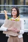 usmívající se žena dívá pryč, zatímco drží nákupní tašku s jídlem venku
