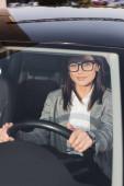 glückliche Geschäftsfrau blickt während Autofahrt auf verschwommenem Vordergrund in die Kamera