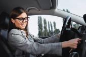 glückliche Geschäftsfrau mit Brille lächelt beim Autofahren