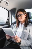pozitivní podnikatelka pomocí digitální tablet při jízdě v autě na zadním sedadle