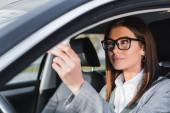 stylische Geschäftsfrau mit Brille sitzt im Auto auf verschwommenem Vordergrund