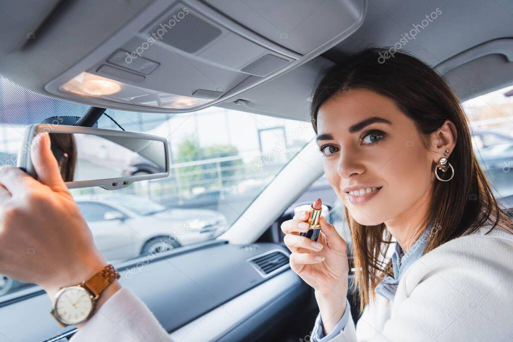 donna sorridente che tiene il rossetto e guarda la fotocamera mentre regola lo specchio retrovisore in auto in primo piano sfocato