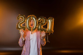 excited man hiding behind 2021 numbers balloons on black