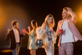 glückliche blonde Frau hält Discokugel neben Mann mit Plastikbecher und multikulturellen Freunden auf verschwommenem Hintergrund auf schwarz
