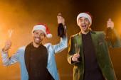 aufgeregte interrassische Männer in Weihnachtsmannhüten mit Champagnerflaschen und Gläsern auf schwarz