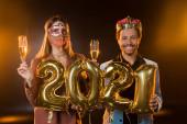 boldog afro-amerikai férfi koronában kezében léggömbök 2021 számok közelében nő karnevál maszk egy pohár pezsgő fekete