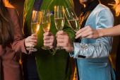 oříznutý pohled na přátele připíjet sklenice šampaňského na černou