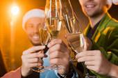 šťastný multikulturní přátelé cinkání sklenice šampaňského na rozmazaném černém pozadí