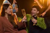 šťastný pár drží sklenice šampaňského, zatímco sedí na pohovce v blízkosti přátel na černé