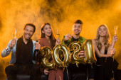 happy interracial friends holding glasses of champagne and balloons with 2021 numbers on orange with smoke