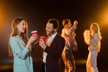 cheerful woman and african american man holding plastic cups near friends dancing during party on black