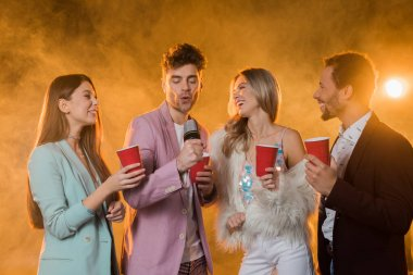 man singing while in microphone near multicultural friends with plastic cups on black with smoke