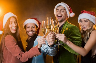 Happy multicultural friends in santa hats clinking glasses of champagne on black stock vector